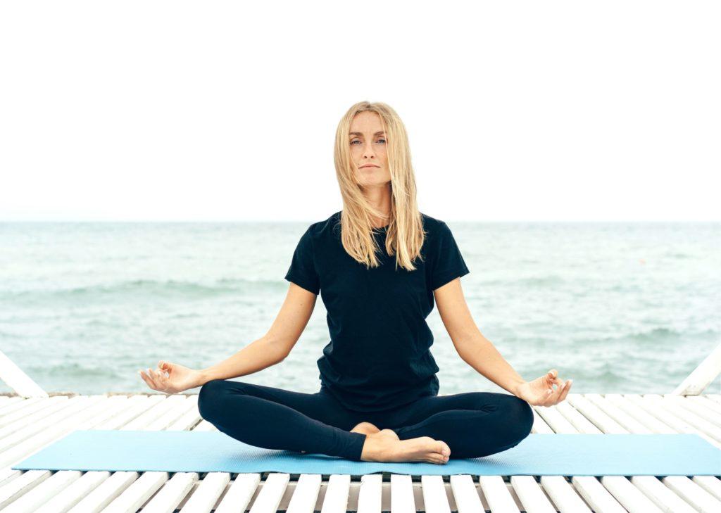 Femme calme et zen faisant du yoga avec une vie bien organisée grace bloc note